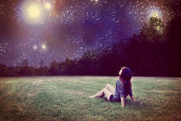 petite-fille-assise-sur-la-pelouse-regardant-les-etoiles